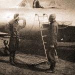 """Подпись в альбоме: """"Аэродром Садовка 1957 г. Инструктор ст. лейтенант Колков принимает доклад от техника самолёта"""""""